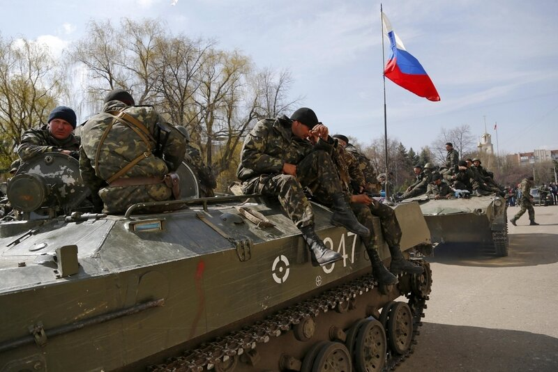 Combat vehicles with a Russian flag on one of them and gunmen on top are parked in downtown of Slovyansk on Wednesday, April 16, 2014. The troops on those vehicles wore green camouflage uniforms, had automatic weapons and grenade launchers and at least on