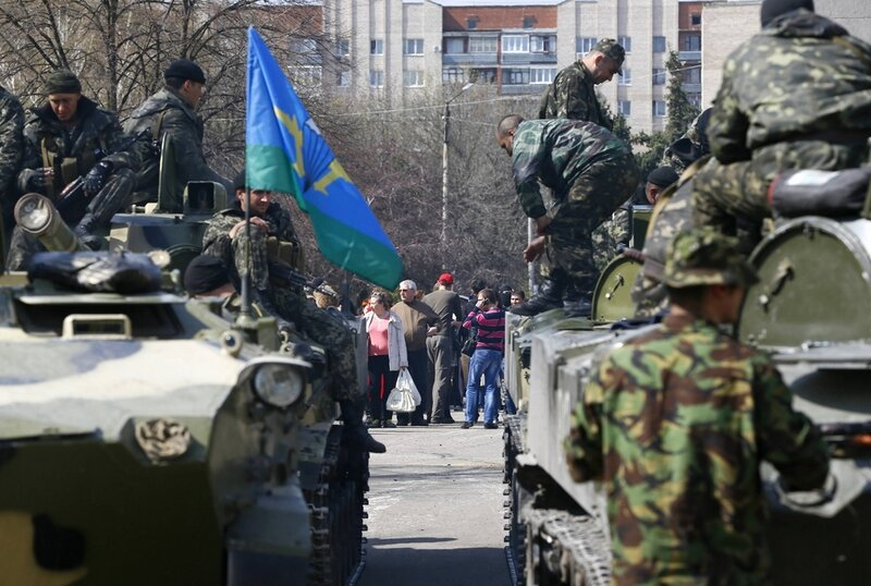 Armed men are seen on and near armoured personnel carriers in Slaviansk