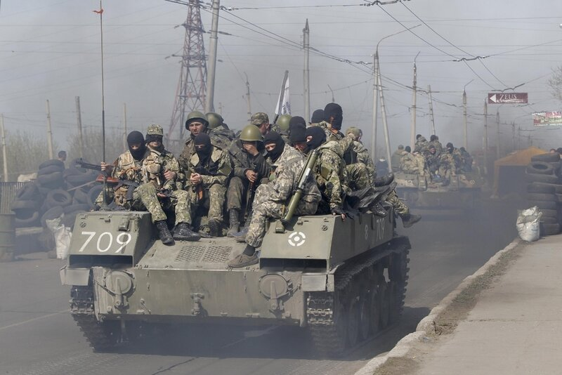 Combat vehicles with gunmen on top make their way through a check-point to the town of Slovyansk on Wednesday, April 16, 2014. The troops on those vehicles wore green camouflage uniforms, had automatic weapons and grenade launchers and at least one had th