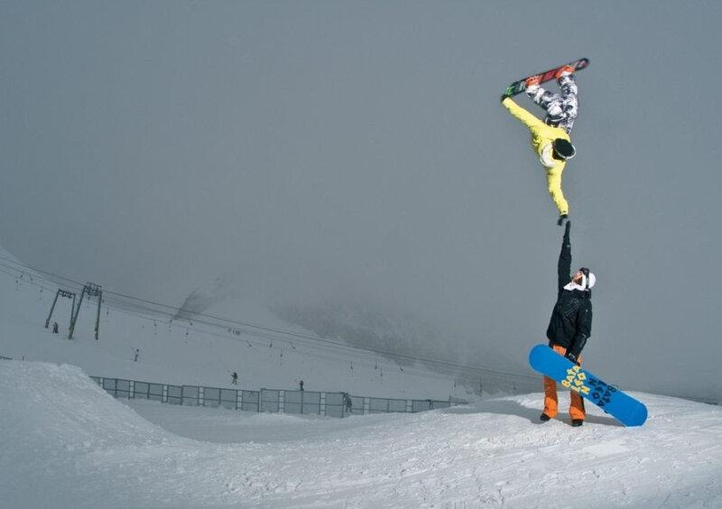 Сноубордист Tyler Chorlton касается руки девушки во время прыжка.