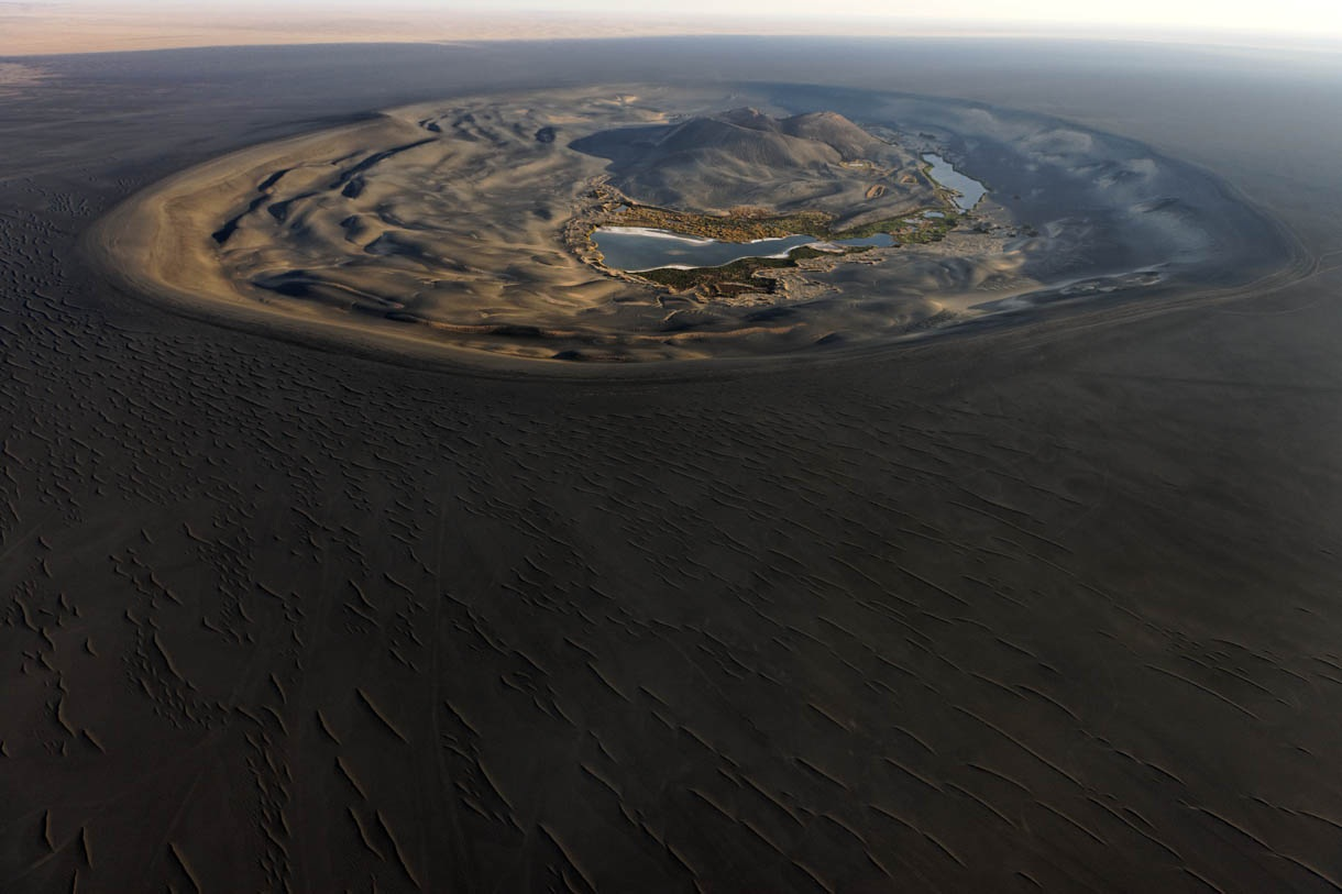 Aerial view of Wau al Namus, (Wau means hole, so Wau al Namus is hole of mosquitos). This massive (and apparently dormant) volcano can be easily be seen in satellite views of Southern Libya, as a large black smear in the wind-scoured sands of the Sahara.