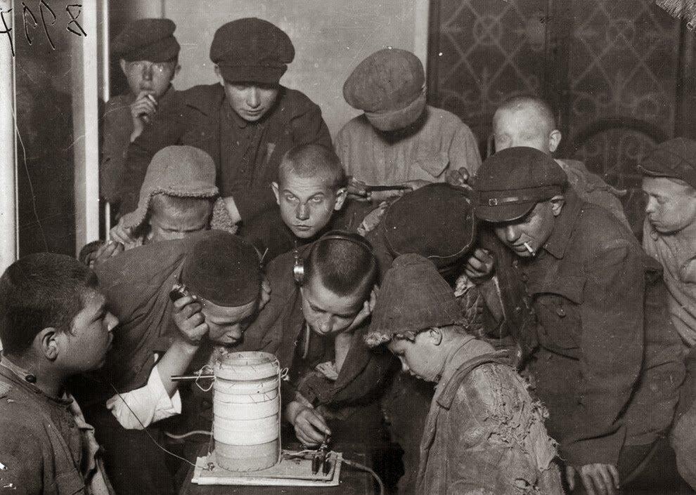 1925. Беспризорники в общежитии у приемника слушают радио «Радонеж». Москва,