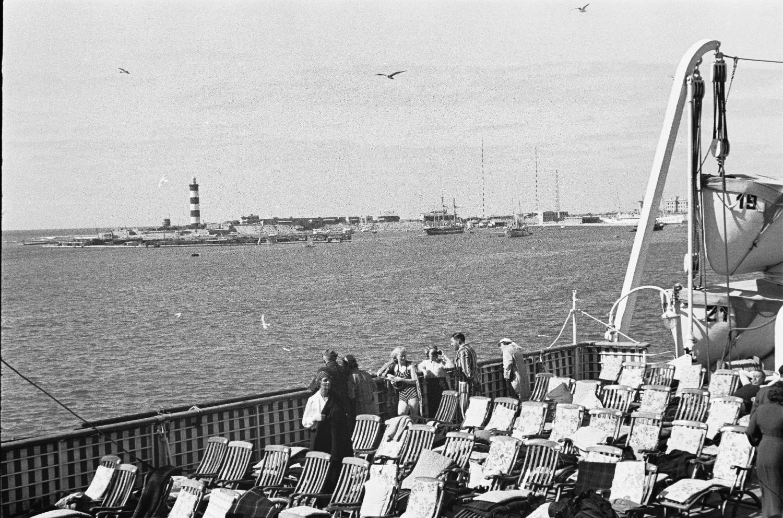 Средиземноморский круиз. Шезлонги на солнечной террасе. Вид на порт с маяком в Средиземном море