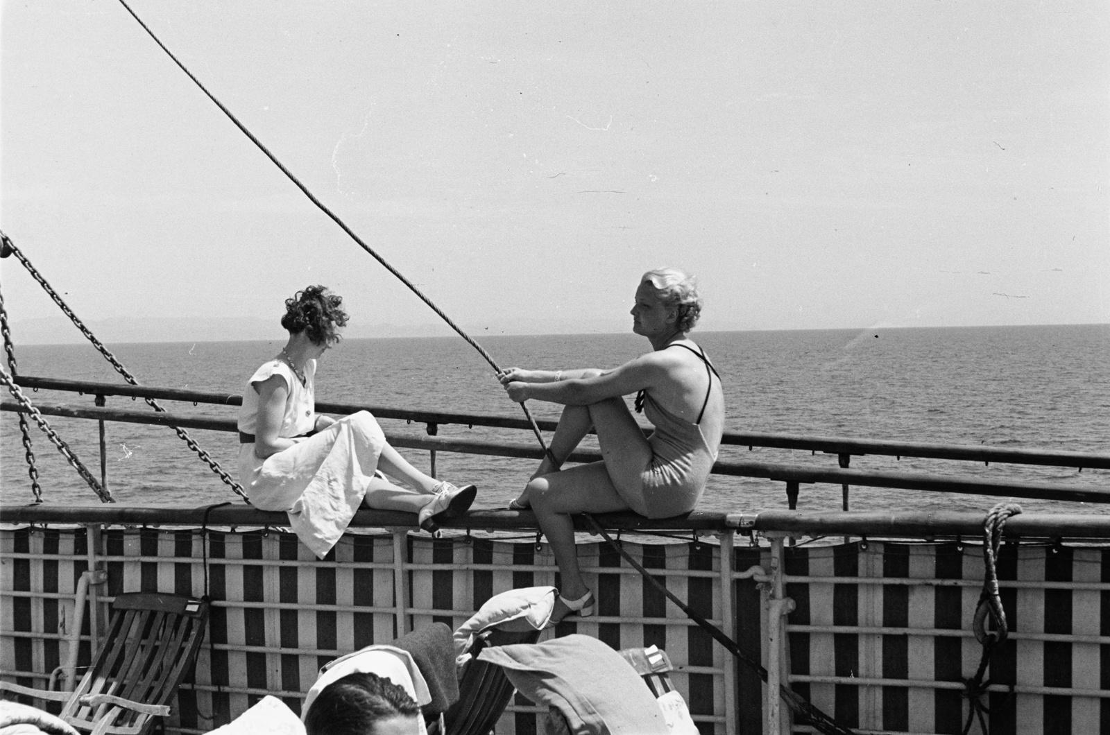 Две молодые женщины, сидящие на перилах