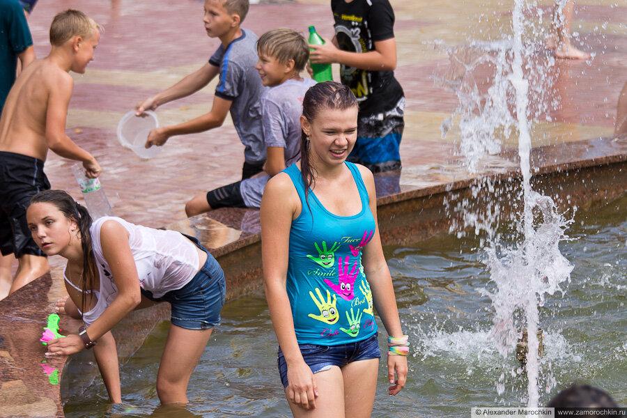 Девушки купаются в фонтане в мокрой одежде