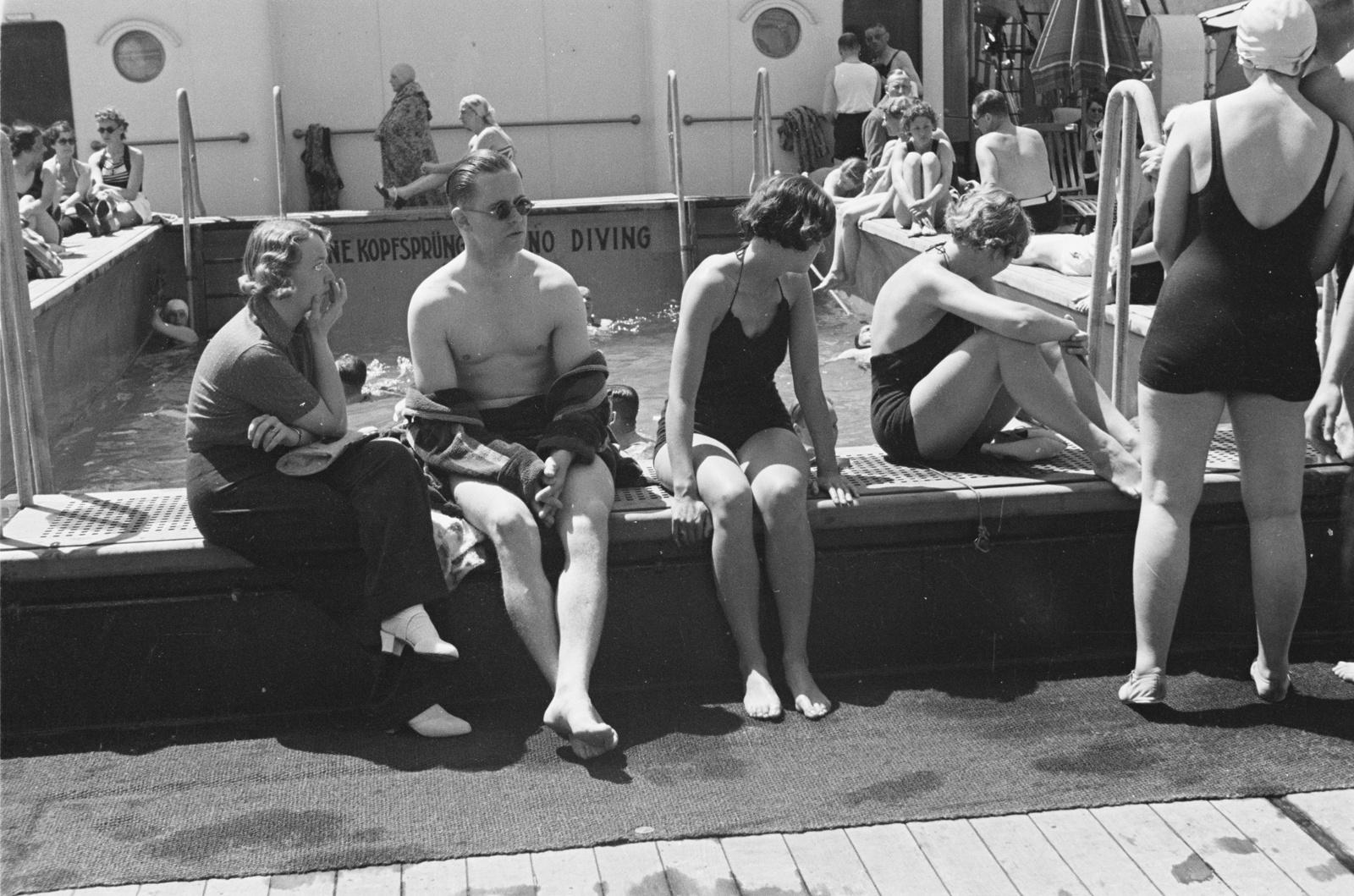 Пассажиры, загорающие на краю бассейна
