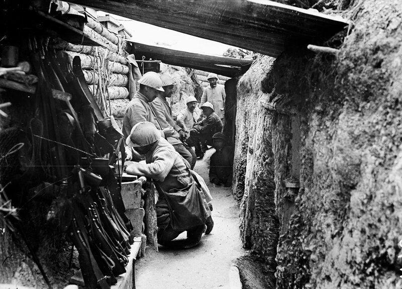 Soldats au repos dans un boyau conduisant aux premières lignes, bois de Vidalet, région de la ferme des Marquises. Au premier plan, les fusils Lebel sont équipés de tromblons Vivien-Bessière permettant de lancer des grenades.