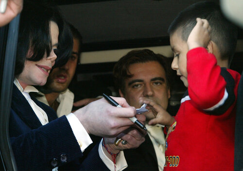 Michael Jackson signs autographs for a fan