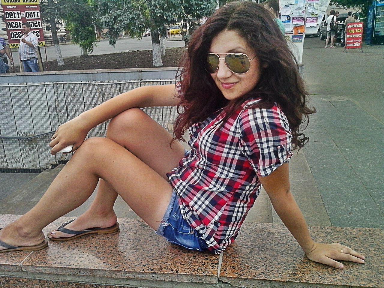 Девушка в клетчатой рубашке и шортах гуляет по городу
