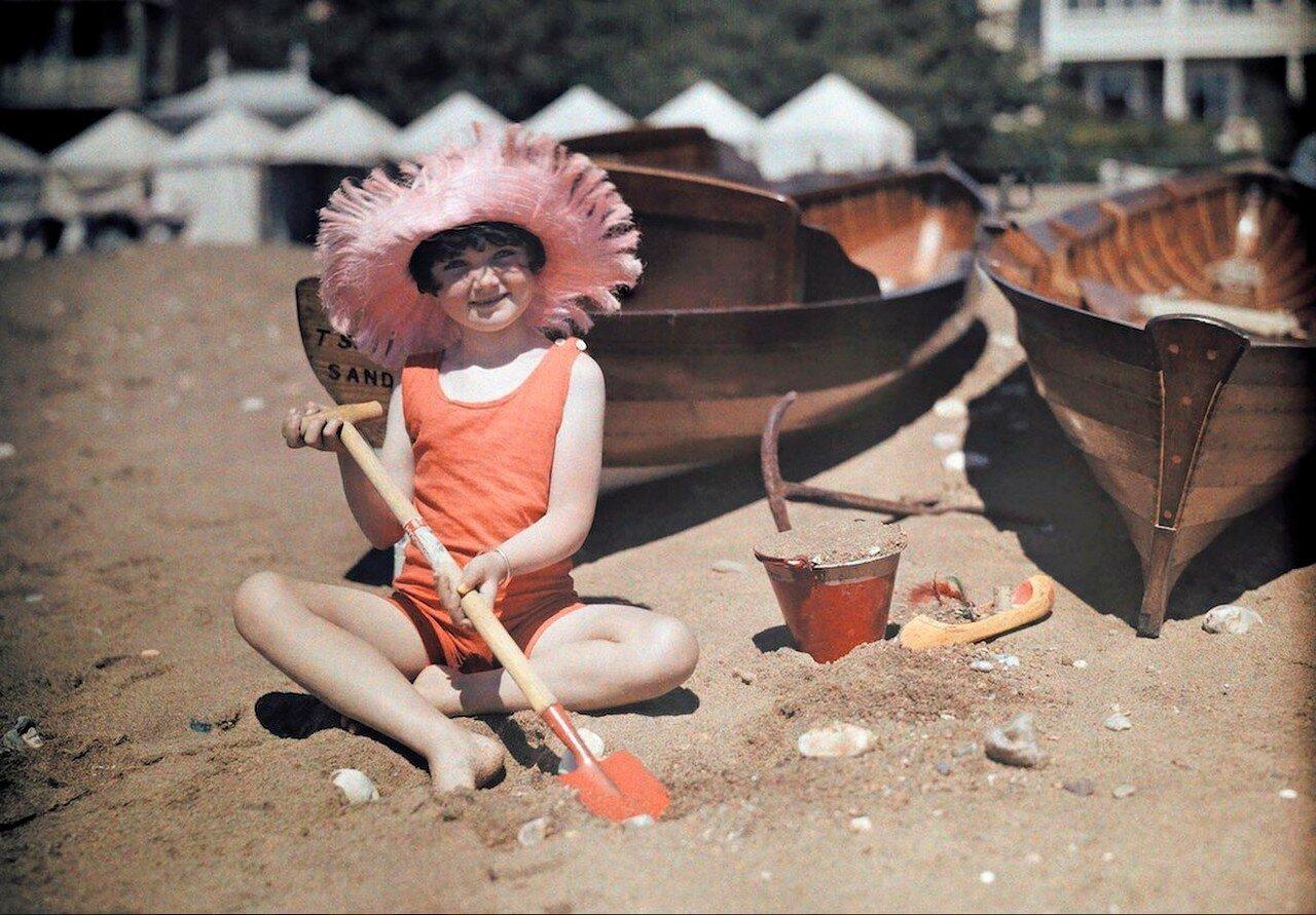 Девочка играет в песке в Сандауне, остров Уайт