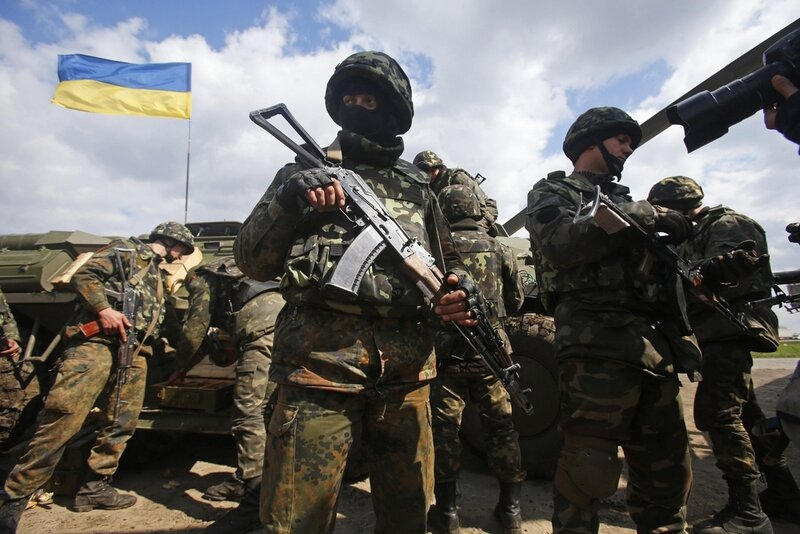 Ukrainian Army troops receive munitions at a field on the outskirts of Izyum, Eastern Ukraine, Tuesday, April 15, 2014. An Associated Press reporter saw at least 14 armored personnel carriers with Ukrainian flags, one helicopter and military trucks parked