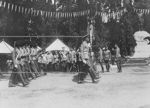 Конно-гренадерский полк проходит церемониальным маршем мимо императора Николая II , стоящего со свитой перед царской палаткой, и памятника шефу полка , великому князю Михаилу Николаевичу в день открытия памятника.