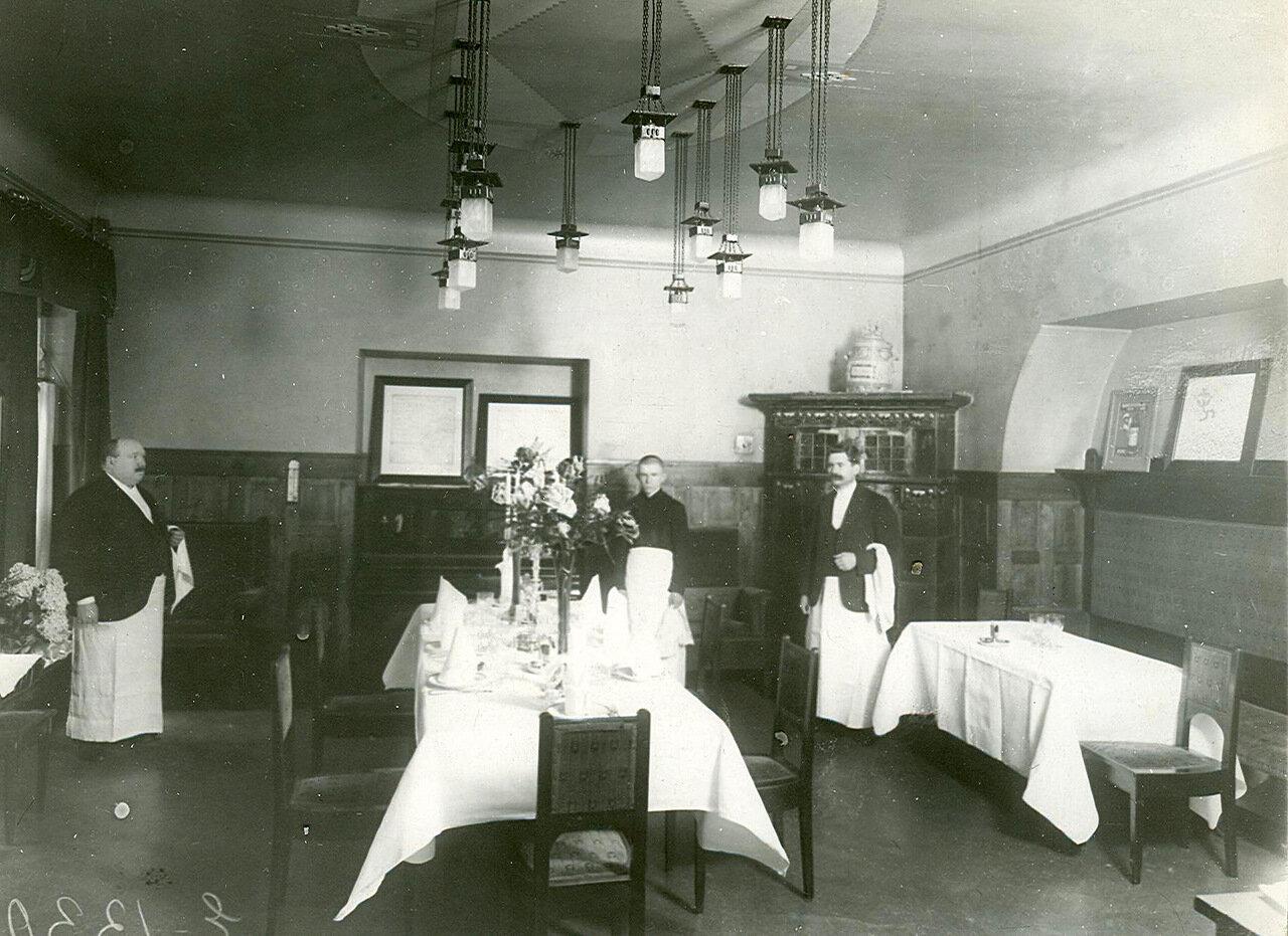 Официанты у стола, накрытого на восемь человек
