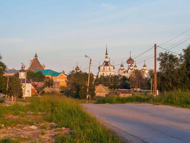 Позади монастырь и дорога освещены вечерним солнцем.