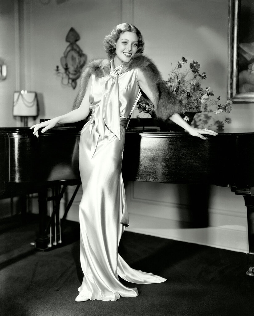 13th August 1934: American actress Loretta Young (1913 - 2000) leans against a grand piano, wearing a full-length evening gown with a fur stole.