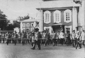 Император Николай ii и цесаревич Алексей в сопровождении свиты и командира полка обходят полк, выстроившийся для парада.