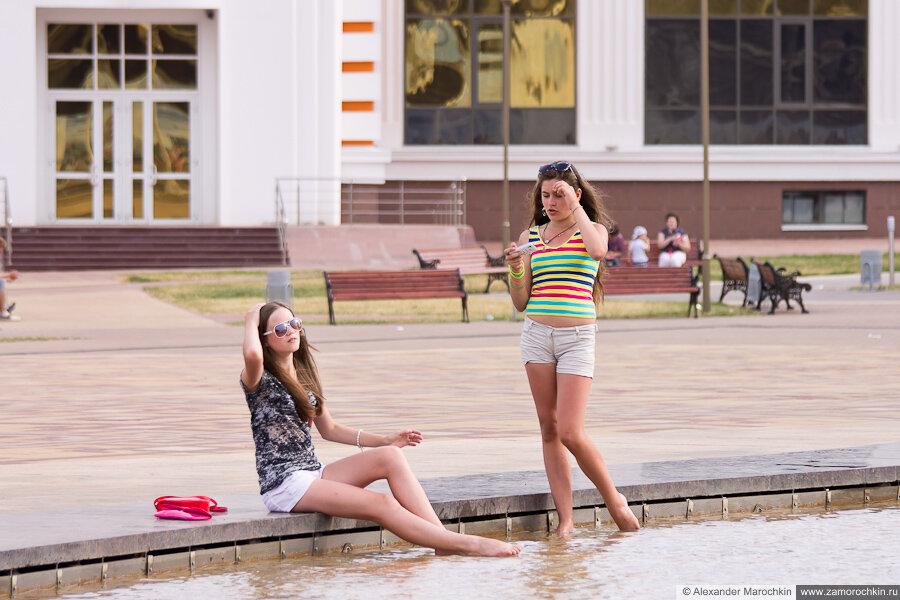 Две девушки охлаждаются в фонтане и фотографируются