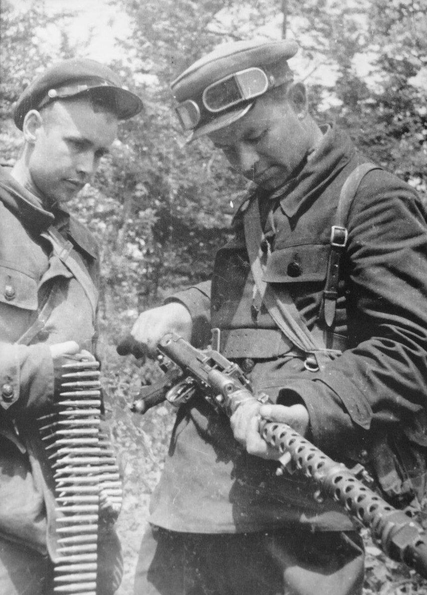 Без даты. Два советских партизана осматривают трофейный немецкий пулемет MG-34
