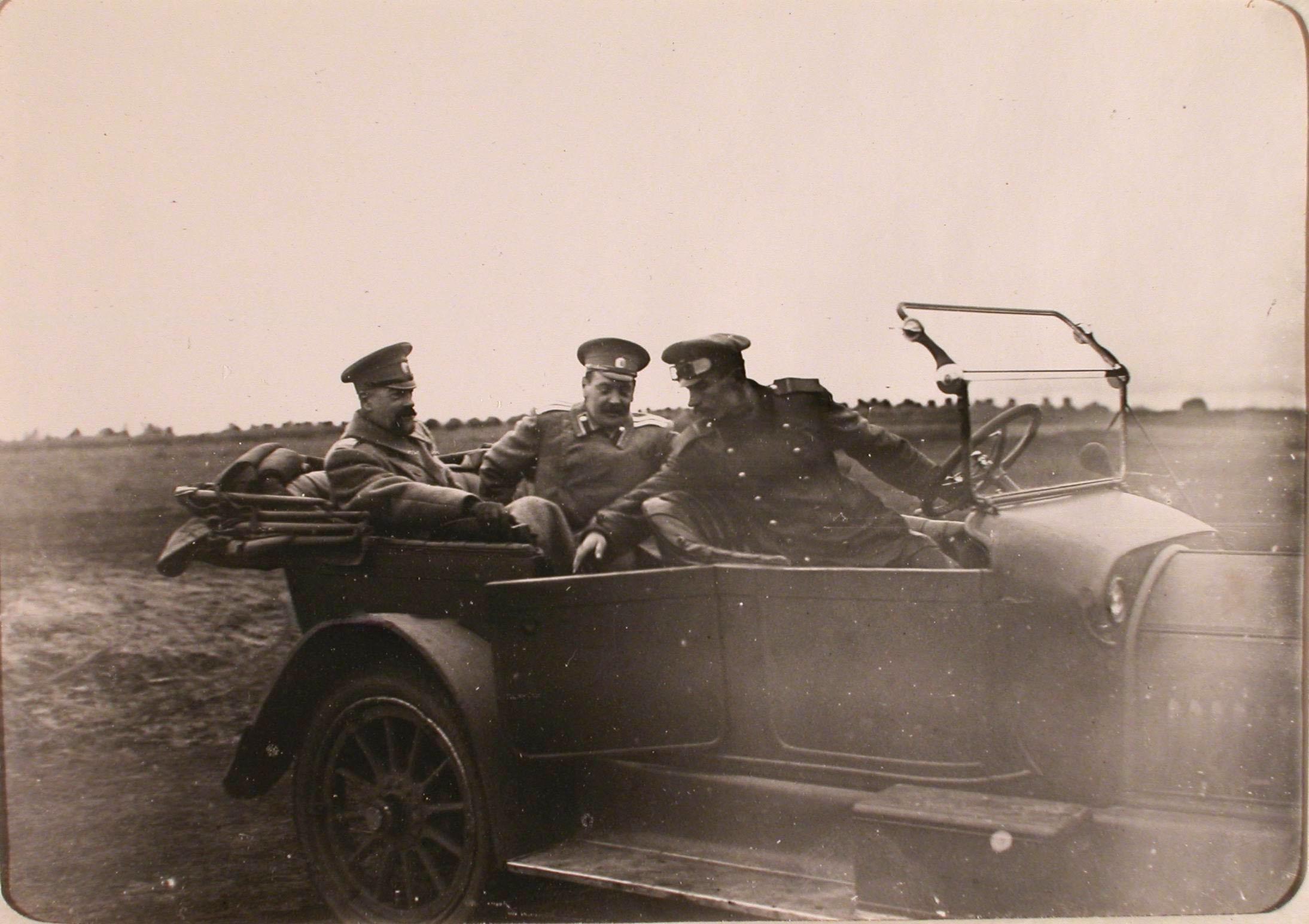 0010Великий князь Александр Михайлович (крайне слева) и сопровождающий его офицер в автомобиле во время приезда на аэродром роты..jpg