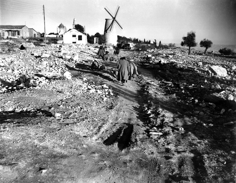 Евреи пригибаются и бегут от арабских снайперов, возвращаясь в свои дома в квартале Монтефиоре на окраине Иерусалима после дневной работы. 20 января