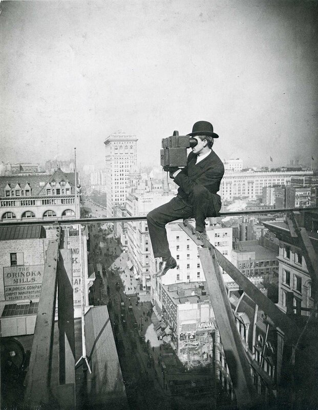 A man taking a photograph from a tall building under construction above Fifth Avenue, looking North, New York City, 1905