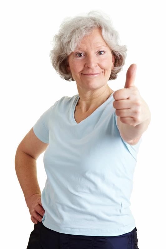 Sportliche Seniorin halt Daumen hoch