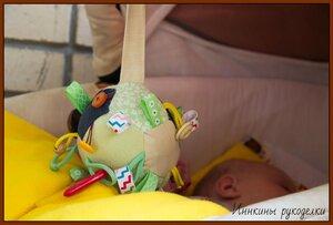 Развивающий мяч рядом с ручкой малыша