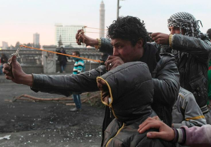 Protesters use slingshots to launch stones at riot police during clashes near Qasr el-Nil bridge, in Cairo