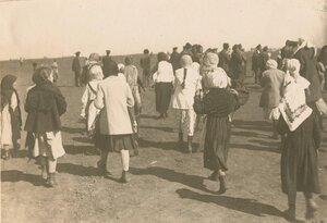 Женщины идут через поле.