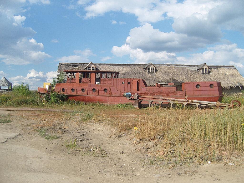 остов старого катера и дом с соломой