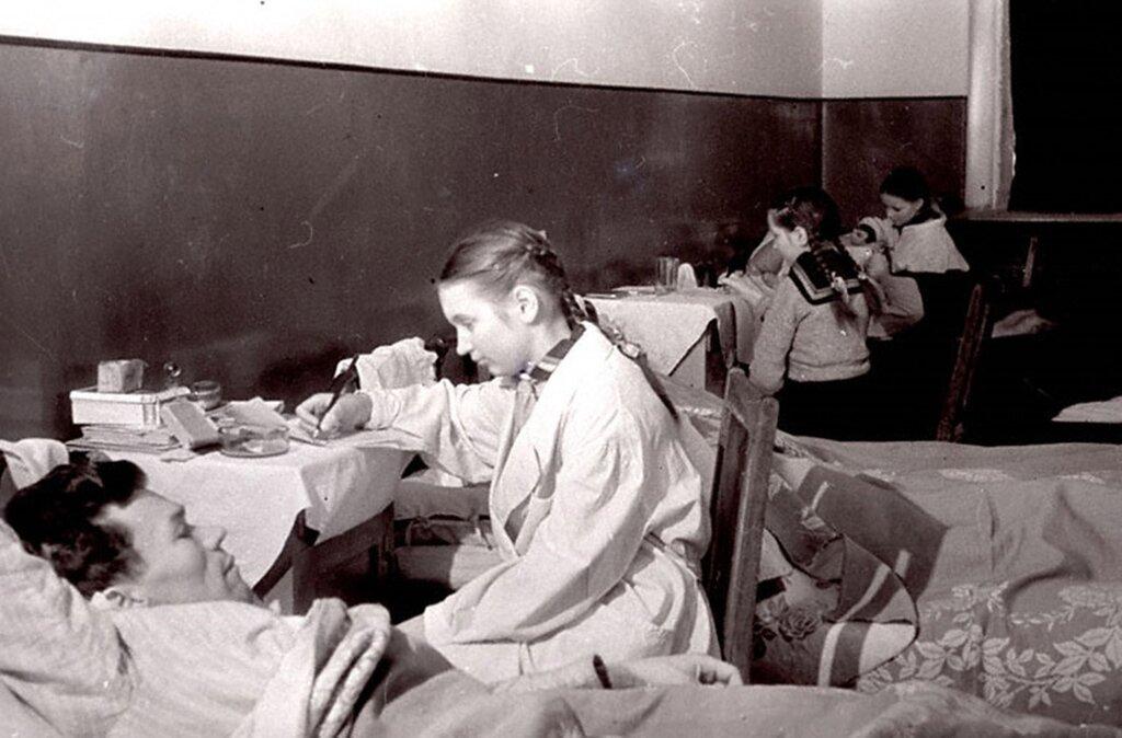 Учащиеся школы № 6 г.Калинина пишут письма домой под диктовку раненых бойцов, находящихся на излечении в госпитале.  1943 г. Калинин.
