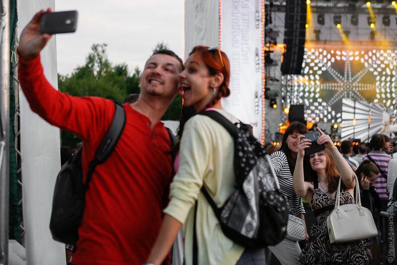 Посетители Фестиваля искусств Черешневый лес фотографируются на фоне сцены в Парке Горького во время концерта