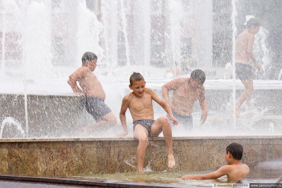 Мальчишки купаются в фонтане