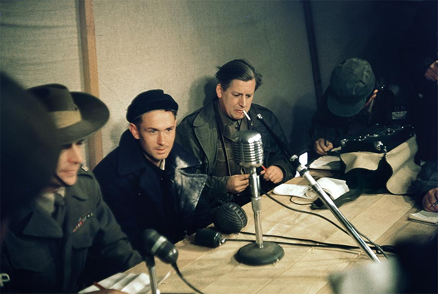 Recently released Australian POW (in the navy blue overcoat) talking to the press, Panmunjom, Korea. ca.1953