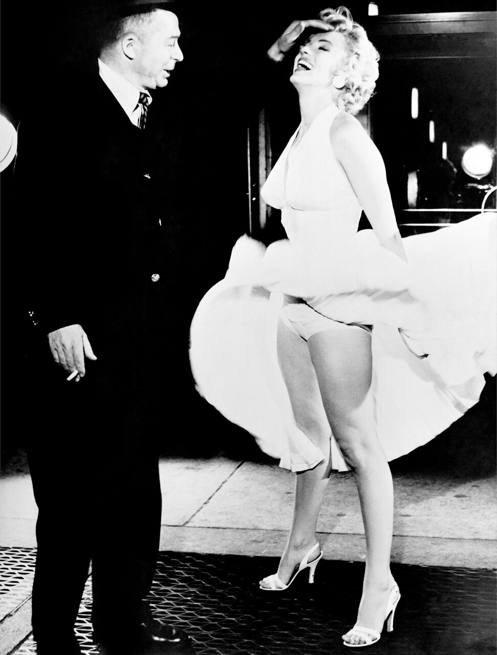 LOS ANGELES - JUNE 3: Actress Marilyn Monroe stand over an air vent which causes her dress to fly up as director Billy Wilder fixes her hair during filiming of the movie 'The Seven Year Itch' which was released on June 3, 1955. (Photo by Frank Worth, Cour