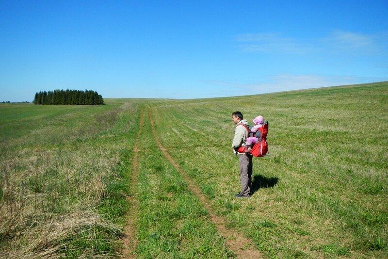 Антон с Динкой за плечами на поле на склоне горы под Чепецком