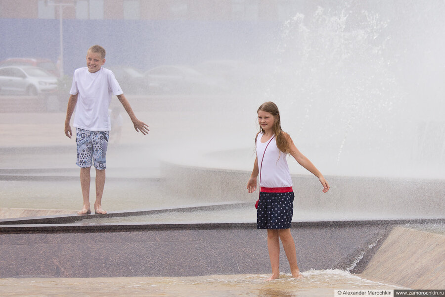 Дети в брызгах фонтана