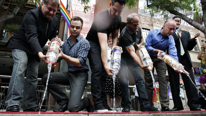 Men empty bottles of Russian vodka filled with water into the gutter during a news conference in West Hollywood