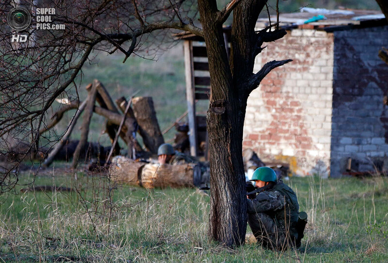 An Ukrainian soldier aim his rifle and takes cover behind a tree as pro-Russia protesters gathered in front of a Ukrainian airbase in Kramatorsk