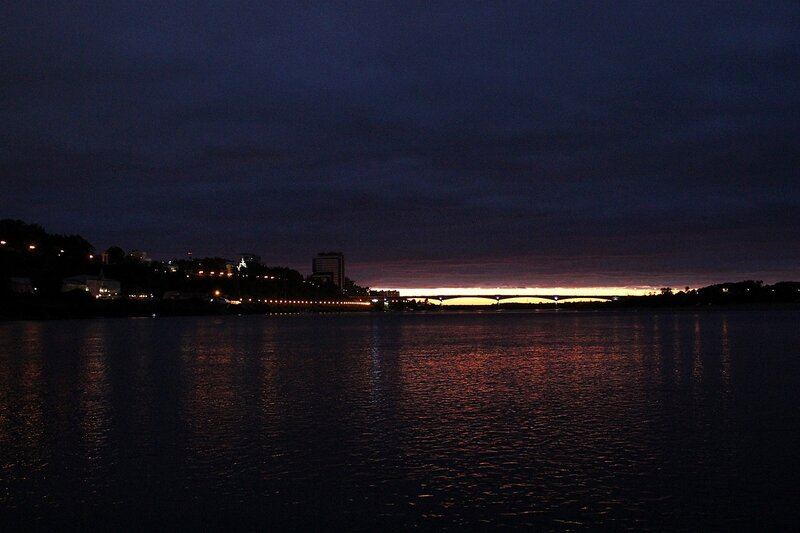 Набережная в ночных огнях и полоска заката за старым мостом