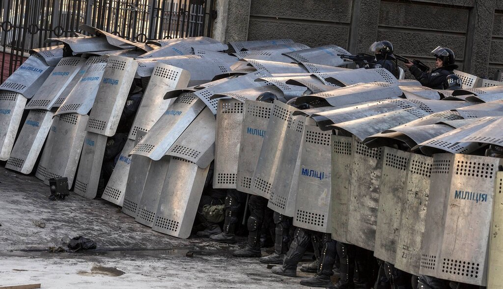 Interior Ministry members take cover behind shields during clashes with anti-government protesters in Kiev