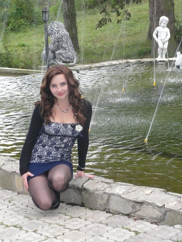Шатенка в синей юбке возле фонтана