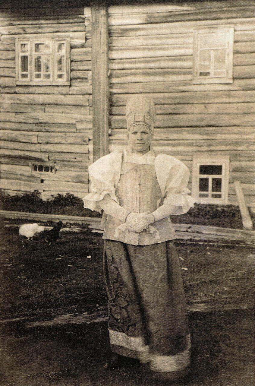 Девушка в праздничном костюме и нарядной повязке. Архангельская губ. Начало ХХ в.