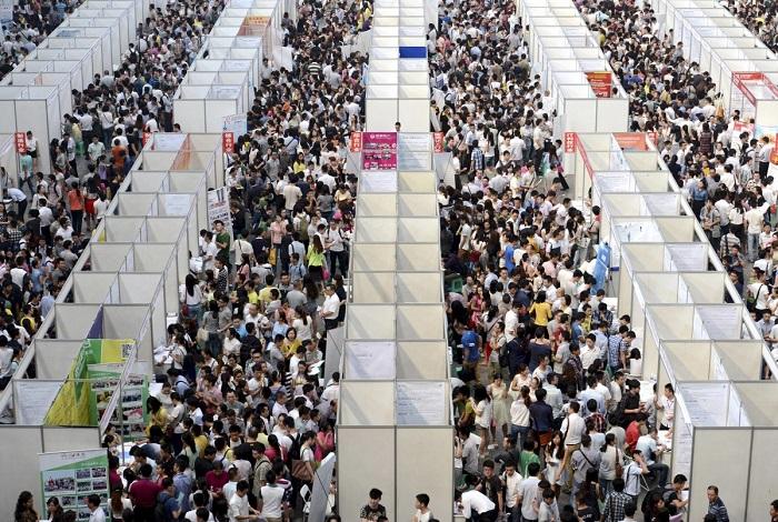 Тысячи лиц, ищущих работу, рассматривают стенды на ярмарке вакансий в городе Чунцин. 12. Полицейски