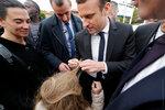 Кандидат в президенты Франции Эманнуэль Макрон распутывает волосы девочки, зацепившиеся за пуговицы его жилета во время визита в больницу Раймонда Пуанкаре недалеко от Парижа. Франция, 25 апреля 2017 года. Фото: Philippe Wojazer / REUTERS    FRANCE-ELECT