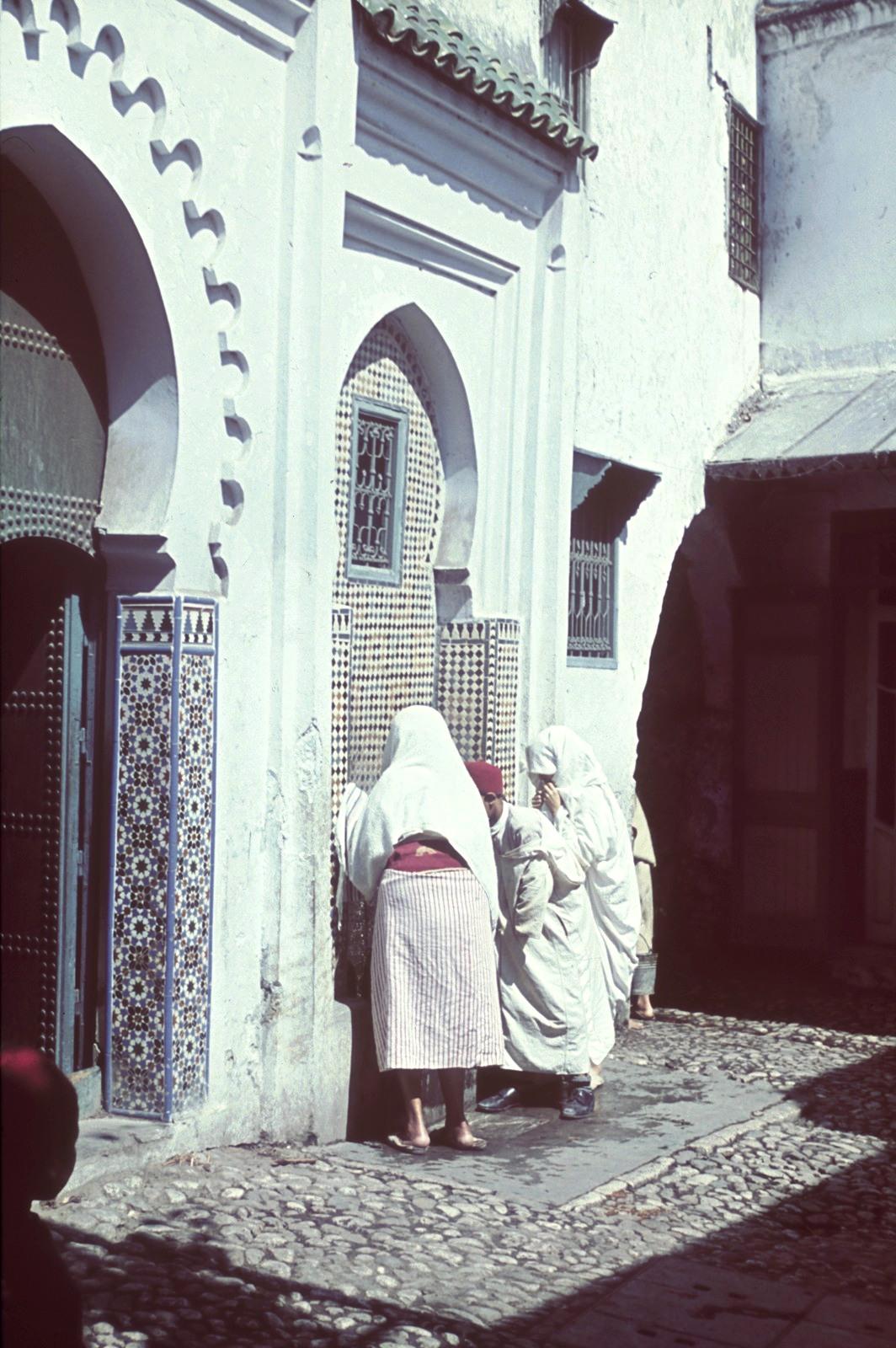 Две женщины и мужчина возле украшенного мозаикой фонтана