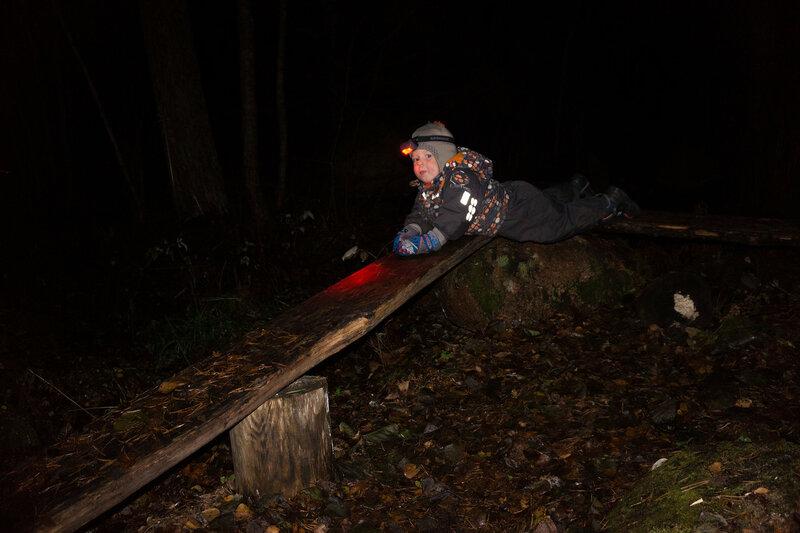 ребенок с налобным фонариком играет в темноте