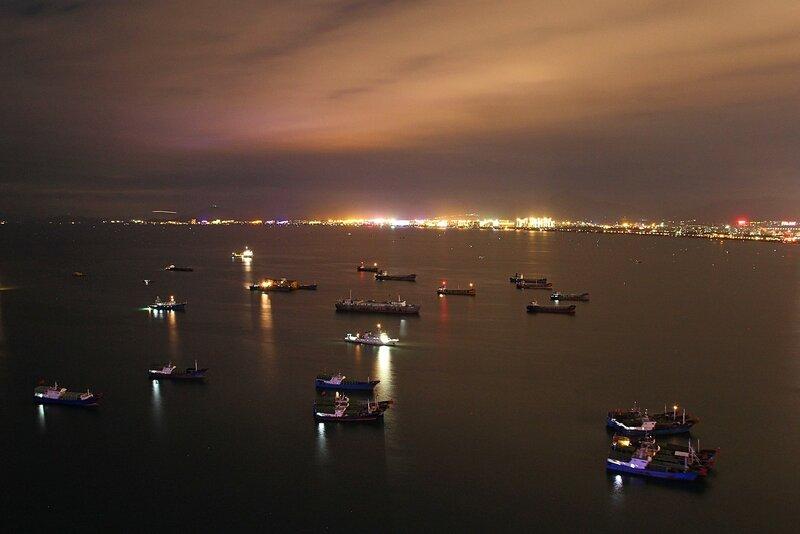 Ночной вид на море и корабли с небоскрёба на насыпном острове Феникс. Бухта Санья, остров Хайнань, Китай