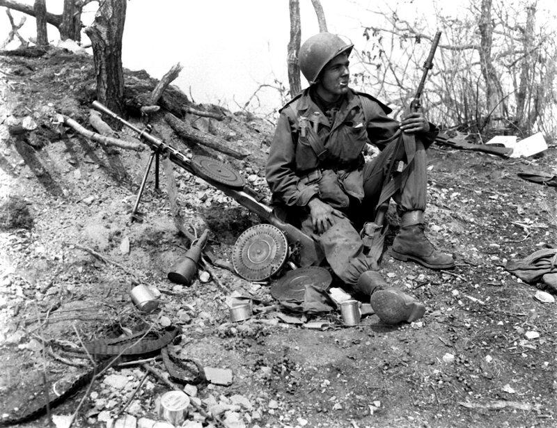 U.S. soldier taking a cigarette break next to some captured equipment. Korean War c. 1950's