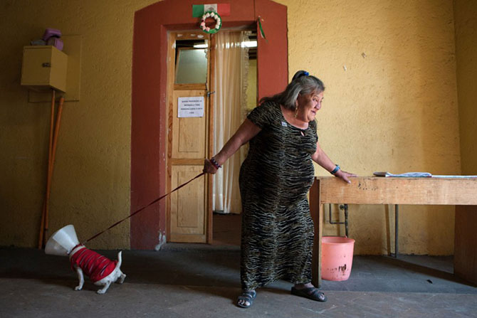Mexico City, 2009, Canela, a resident at CasaXochiquetzal, takes a visiting dog on a walk. Originally from Oaxaca, Canela came to Mexico City to work at a very young age. She is now well known and respected in the neighborhoods that surround Casa Xochique